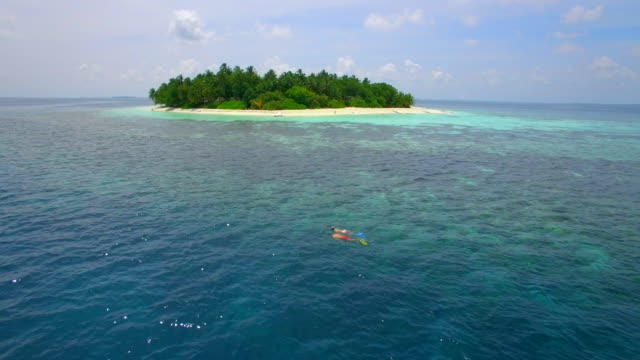 Aerial drone view of a man and woman couple snorkeling over a coral reef of a tropical island.