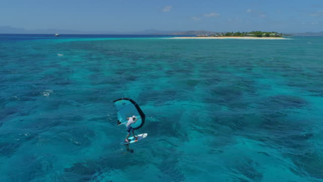 Aerial drone view of a man kite board wing surfing hydrofoiling near an island in the Pacific Ocean.