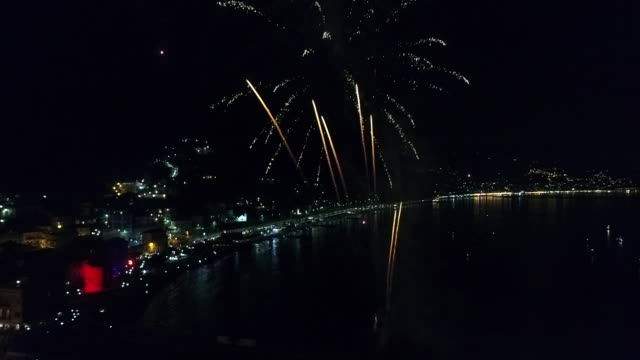 Aerial drone view of fireworks over coastal town Camogli and sea