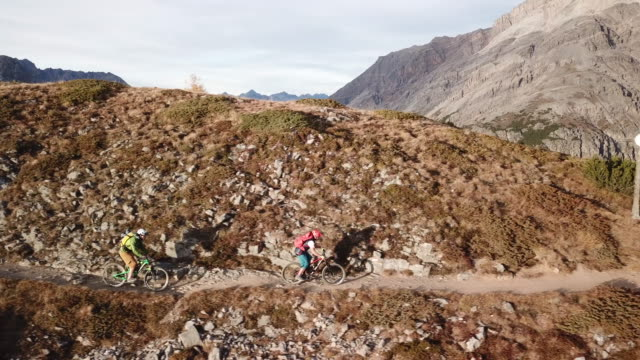 Aerial drone view of mountain bikers riding mountain ridge