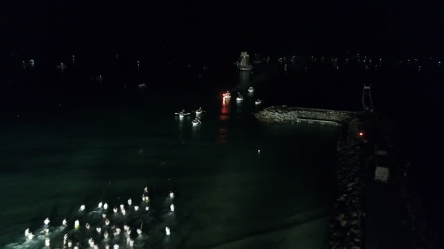 Aerial drone view of swimmers racing into sea at night