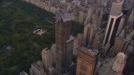 Aerial -Early evening over mid-town Manhattan, a cirling ZI to biuldings around The Pond in Central Park.