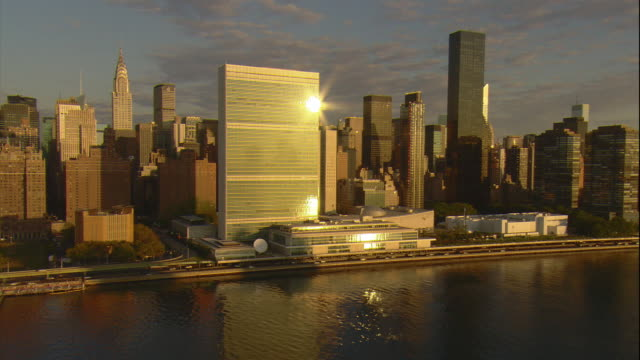 Aerial -Early morning passing shot of United Nations headquarters in mid-town Manhattan as seen from low over the East River.