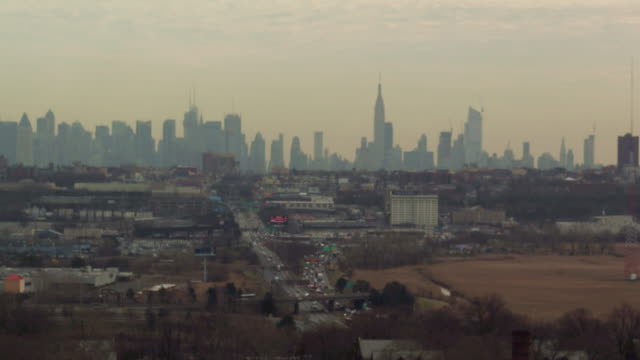 Aerial floating over yellow field and industrial suburb with NYC skyline in the distance