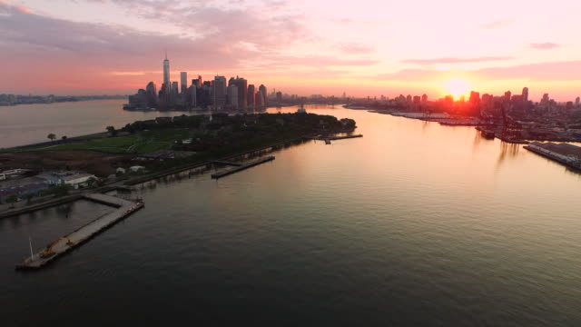Aerial flying away from Manhattan over East river and boat at sunrise