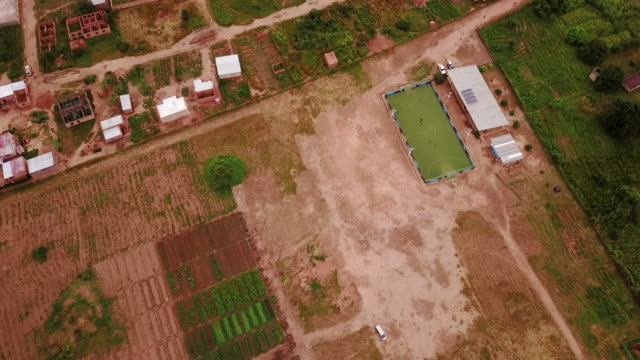 Aerial flying high over farm and football field, in Congo Africa daytime