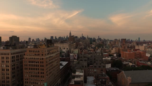 Aerial flying low over buildings at sunset in Manhattan NYC