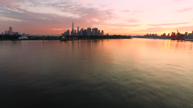 Aerial flying low over East River towards Manhattan at sunrise