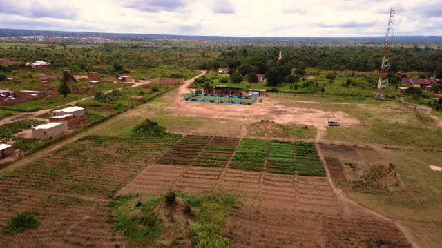 Aerial flying low over farm and football field, in Congo Africa daytime