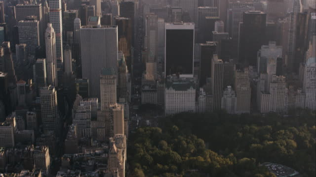 Aerial Flying over Central park and 5th Avenue heading South and tilting up to Midtown and Lower Manhattan, NYC