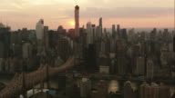 Aerial flying over East River and Roosevelt Island looking West at Sun setting over Midtown Manhattan, NYC