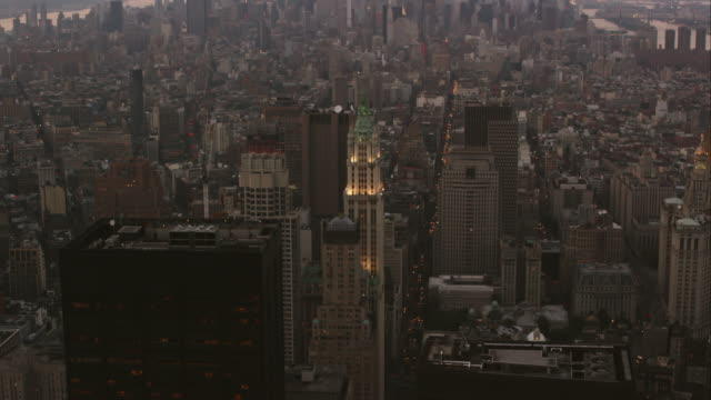 Aerial flying over financial district looking north over Manhattan as camera pans slowly down on Woolworth Building, NYC