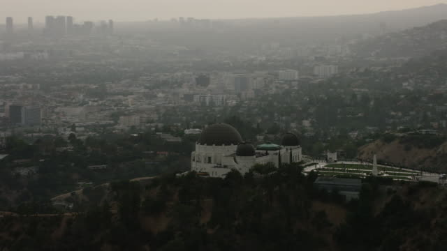 Aerial flying over Griffith Park looking out over Los Angeles, CA late afternoon