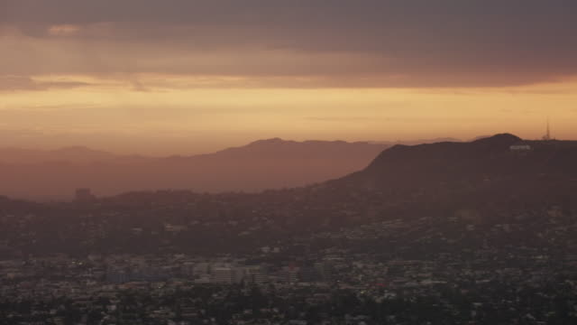 Aerial flying over Los Angeles CA, camera panning over the  Hollywood hills sunset