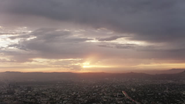 Aerial flying over Los Angeles CA, camera tilts down over Hollywood, sunset