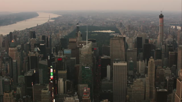 Aerial flying over midtown Manhattan looking North past Central Park at sunset in NYC