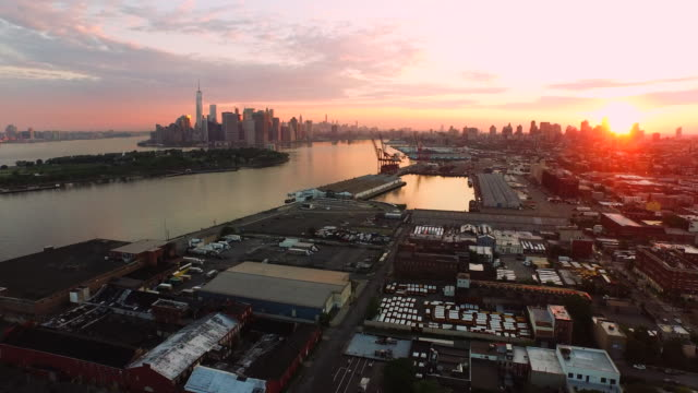Aerial flying over Red Hook Brooklyn at sunrise view of lower Manhattan