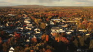 Aerial flying over residential area surrounded by  Fall Foliage