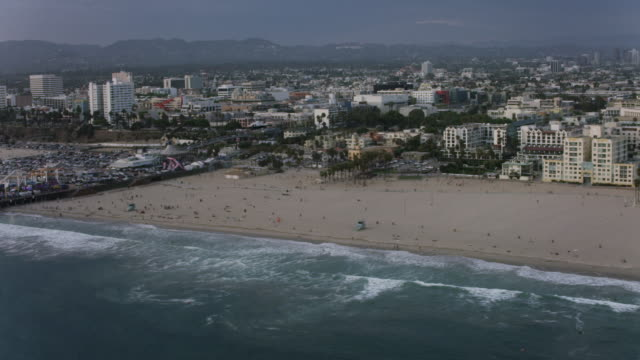 Aerial flying over Santa Monica looking at helicopter mid air LA, CA sunset