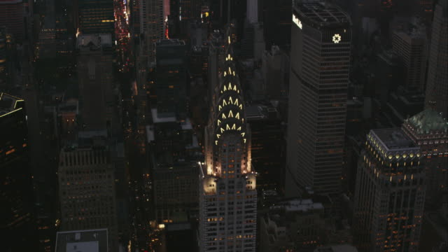 Aerial flying over the Chrysler Building with it lights on in Manhattan NYC