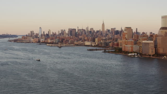 Aerial flying over the Hudson River, view of Midtown Manhattan, sunset NYC