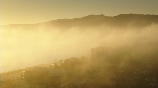 Aerial POV flying over the Pacific Ocean and beach at Santa Monica, CA, at Sunset, with the backlit fog rolling in.