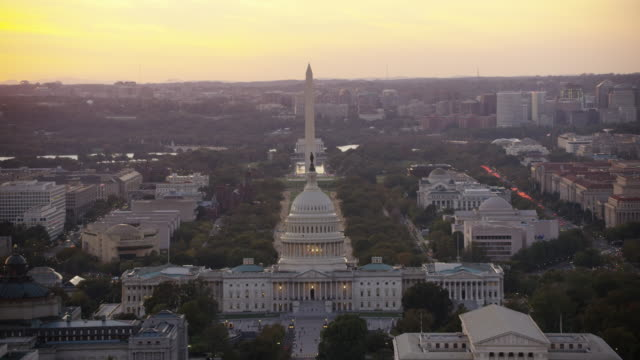 Aerial flying over Washington DC wide view of United States Capitol, sunset USA