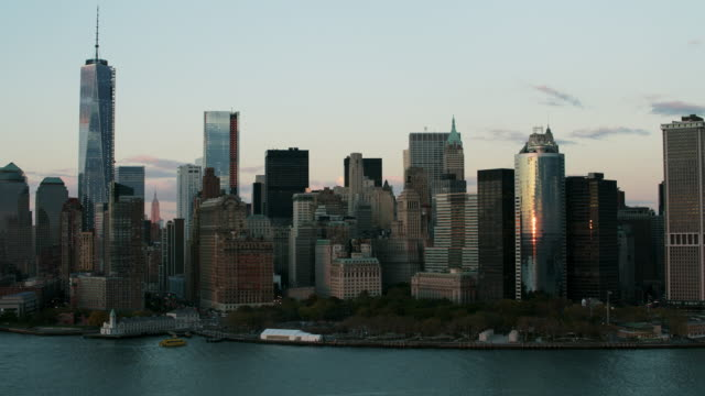 Aerial flying past southern tip of Manhattan, World Trade, financial centers, and Battery park at the end of the day
