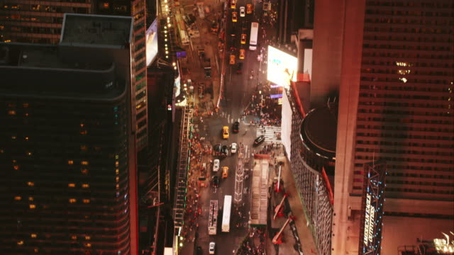 Aerial flying south down Broadway and looking down as we fly over Times Square at night with lights on, NYC