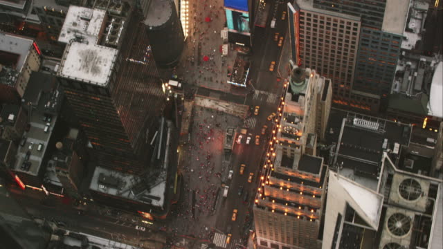 Aerial flying south on Broadway looking down at Times Square with lights on in NYC