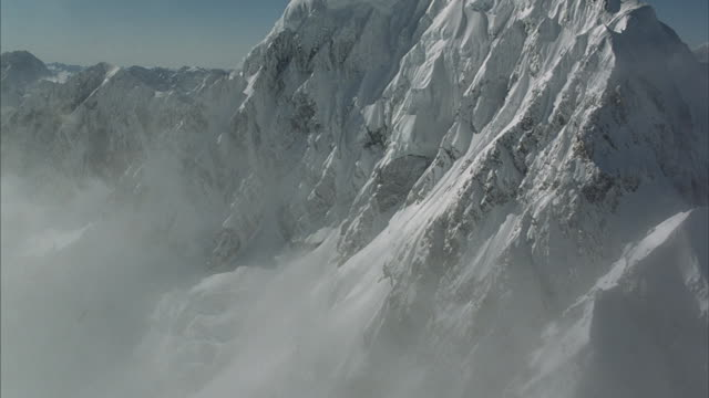 Aerial flying through clouds and past the side of a rugged snow-covered mountain peak.