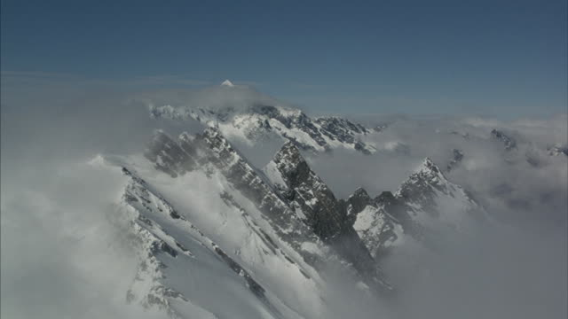 Aerial flying through clouds towards a partially obscured rocky snow-covered mountain peak.