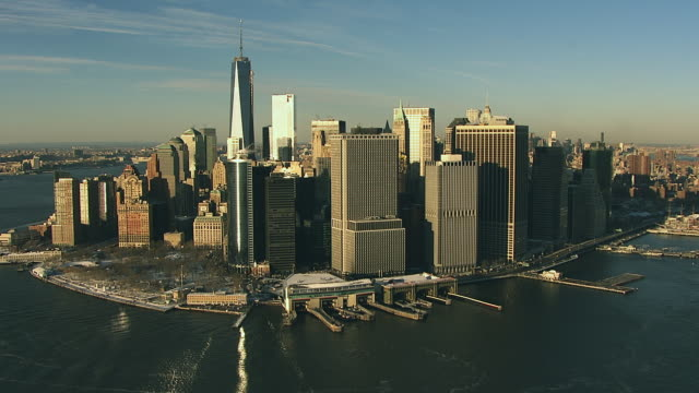 Aerial flying towards south end of Manhattan, financial district covered in snow over East River
