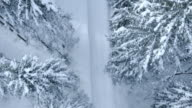 Aerial following the snowy forest road