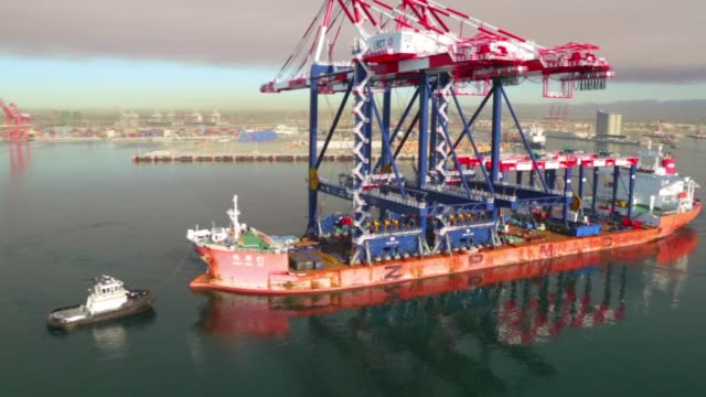 Aerial footage of Two of the worlds largest STS gantry cranes manufactured by ZMPC in China being delivered to the Long Beach Container Terminal at...