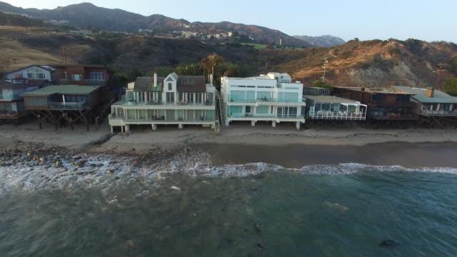Aerial footage over Malibu houses on the beach