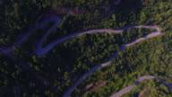 Aerial footage recorded with drone flying over a stunning mountain road between forest and cliffs in the monumental mountains in the Serra de Montsant in Tarragona during travel vacations. 4K UHD.
