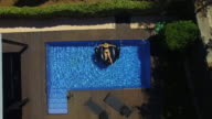 Aerial footage taking with drone of a happy girl enjoying summer in swimming pool with big inflatable black swan sunbathing and relaxing in the sun during weekend. 4K UHD.