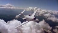 Aerial high angle private jet in flight banking in air through clouds
