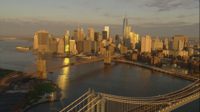 Aerial -Just after sunrise, flying south down the East River over the Manhattan and Brooklyn bridges while looking toward the lower Manhattan skyline including the Freedom Tower.