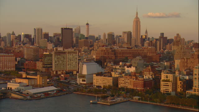 Aerial -Just before sunset, low tracking shot along the West Side Highway as it enters the Meat Packing district, with mid-town Manhattan and the Empire State building in BG.