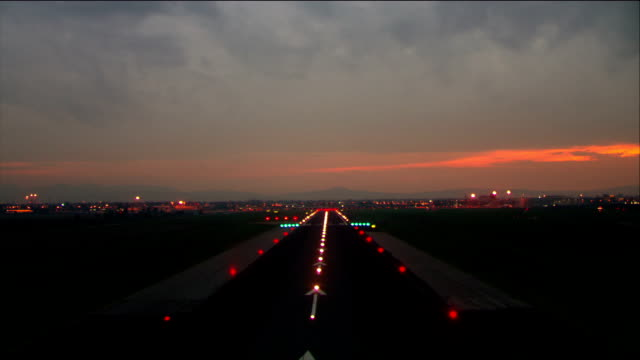 Aerial landing on runway at Florence Airport at night / Florence, Italy