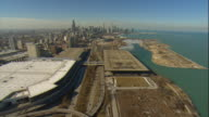Aerial -Late winter afternoon wide view of Lake Michigan shoreline passing over McCormick Place and the Convention Center with Chicago skyline behind.
