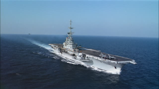 Aerial long shot FS Clemenceau sailing through ocean / Dassault jet landing on deck / France