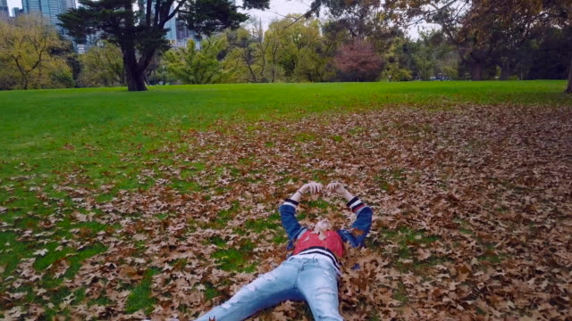 Aerial low angle view of a young millennial woman laying down and playing with autumn leaves