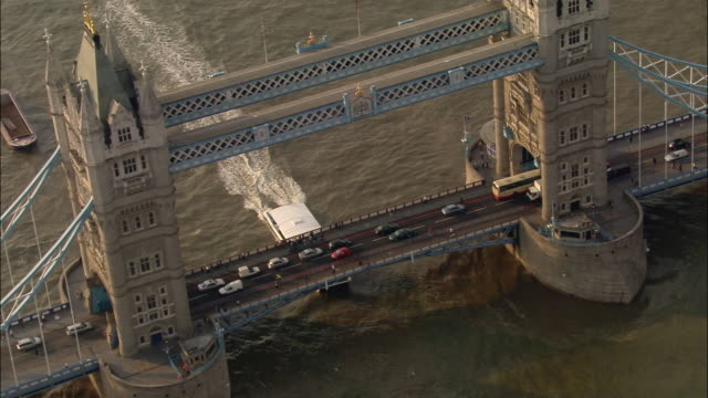 Aerial medium shot traffic passing over and boat passing under Tower Bridge / zoom out wide shot panning Tower Bridge and surrounding cityscape / London