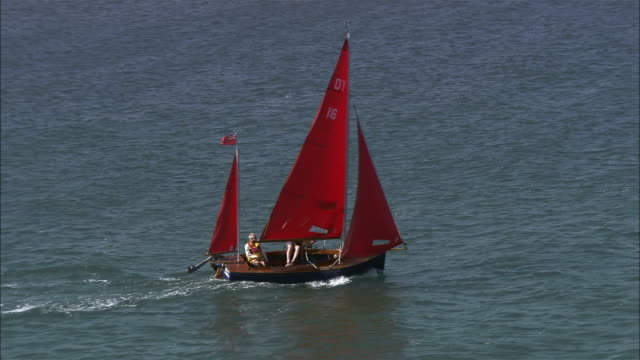 Aerial medium shot zoom out people sailing boat with red sails in Wells Harbour/ Wells next the sea, Norfolk, England