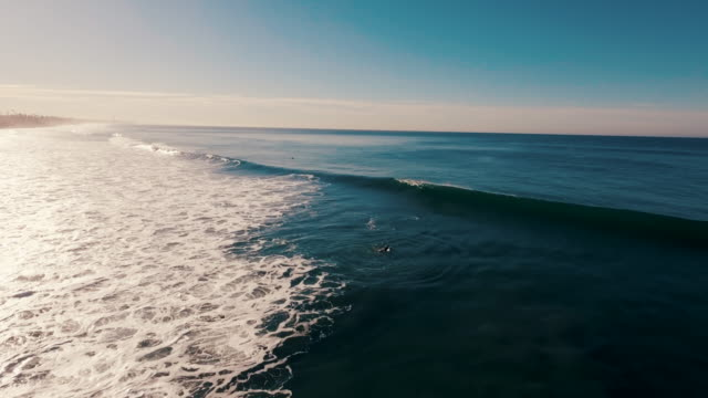 Aerial of a beautiful sunrise sparkling off the ocean as a surfer paddles out into the lineup and a big wave crashes over his head, all glowing in the early morning light.