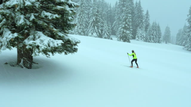 Aerial of a woman cross country skiing uphill
