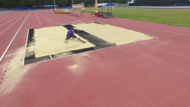 Aerial of amputee athlete practicing long jump